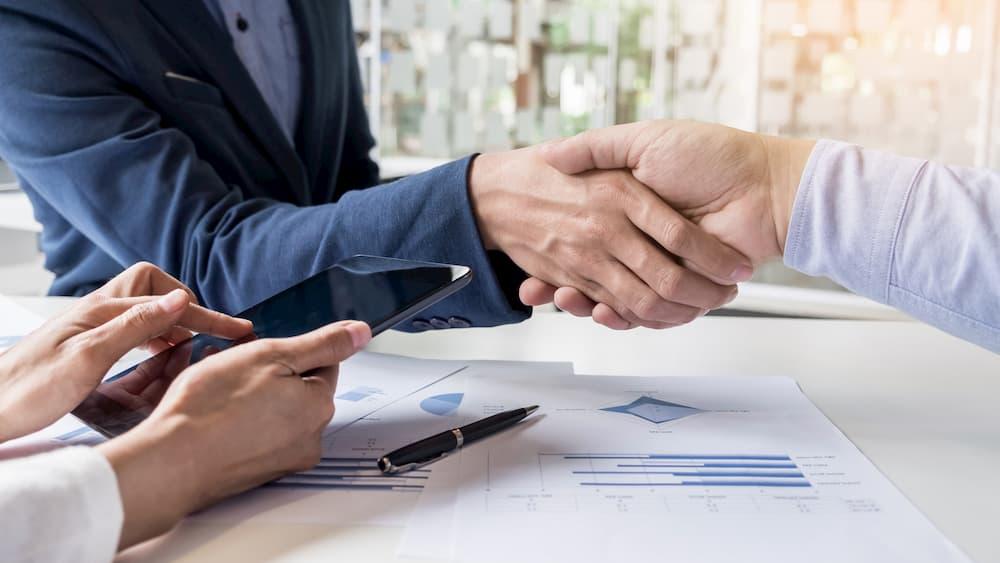 homens apertando mão incinuando acordo